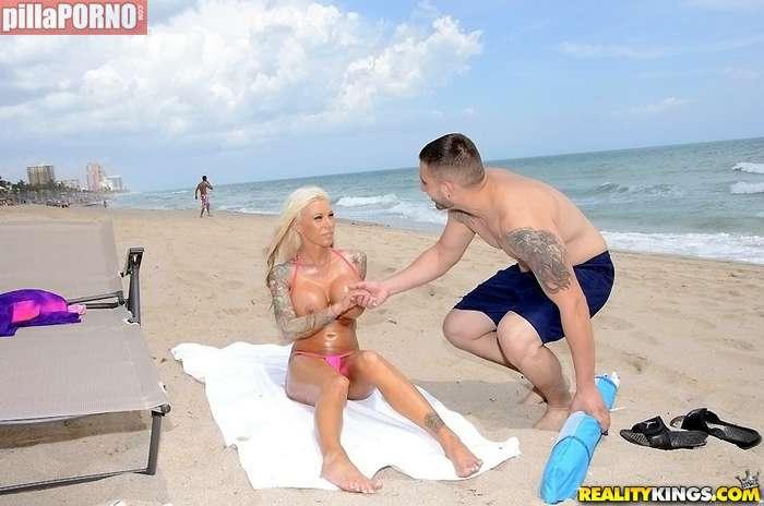 Dandole cremita a una joven en la playa - foto 2