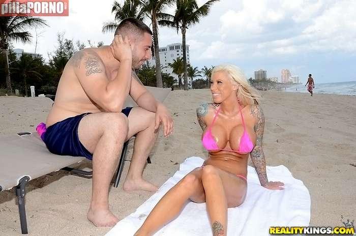 Dandole cremita a una joven en la playa - foto 3