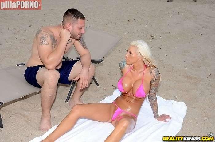 Dandole cremita a una joven en la playa - foto 4
